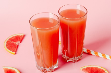 Refreshing grapefruit juice with straws on a pink background with grapefruit slices. Summer refreshing diet drink, healthy food