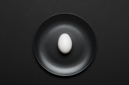 White egg on a black plate on a black background. Concept healthy food, diet. Top view, flat lay Stock fotó