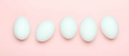 White eggs on a pink background. Banner. Healthy food. Top view, flat lay.