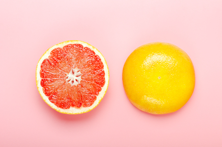 Halved grapefruit on a pink background. Refreshing summer tropical fruit. Minimal composition. Top view, flat lay. Stock fotó