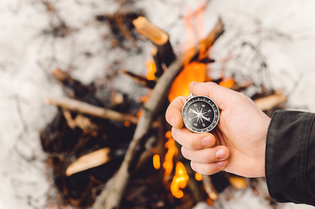 A man holds a compass by the burning bonfire in winter. Concept hike, walk, journey