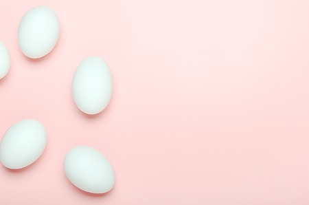White eggs on a pink background. Healthy food. Copy space, top view, flat lay.