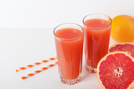 Grapefruit refreshing juice with straws on a white background with grapefruit slices. Summer refreshing diet drink, healthy food. Copy space.