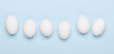 White eggs on a blue background. Banner. Healthy food. Top view, flat lay. Stock fotó