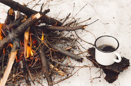 Walking mug with coffee near the campfire. Concept hike, walk, trip in winter