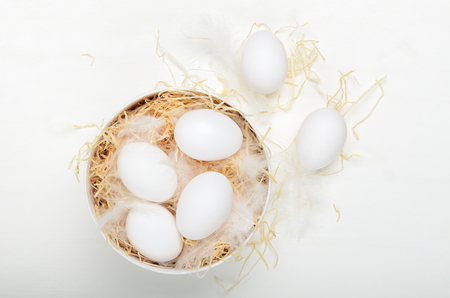 Eggs in a round box with hay on a white background. Concept easter composition, spring holiday, healthy food. Top view, flat lay.