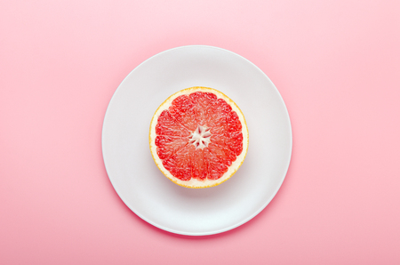 Half a grapefruit on a pink plate on a pink background. Refreshing summer tropical fruit. Minimal composition. Top view, flat lay. Stock fotó - 126127460