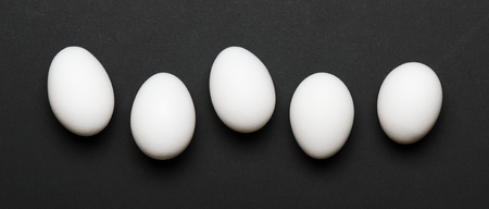 White eggs on a black background. Banner. Healthy food. Top view, flat lay