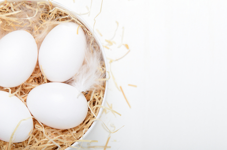 Eggs in a round box with hay on a white background. Concept easter composition, spring holiday, healthy food. Copy space, top view, flat lay. Stock fotó