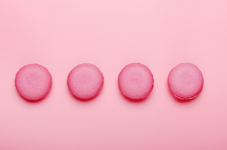Pink macaroon cookies on a pink background. The concept of sweets, pastries, junk food. Minimal composition. Top view, flat lay