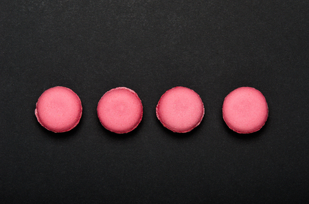 Pink macaroon cookies on a black background. The concept of sweets, pastries, junk food. Minimal composition. Top view, flat lay