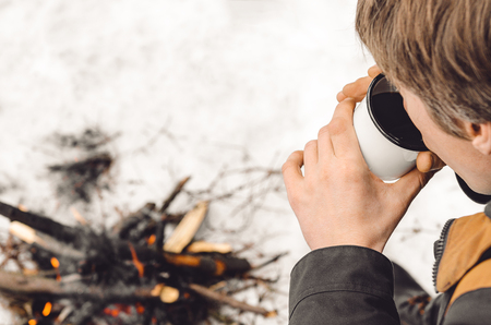 A man drinks coffee from a white mug by the burning campfire in the winter. Concept hike, walk, journey Stock fotó