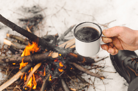 Male hands hold a mug of coffee near a burning campfire. Concept hike, walk, trip in winter.