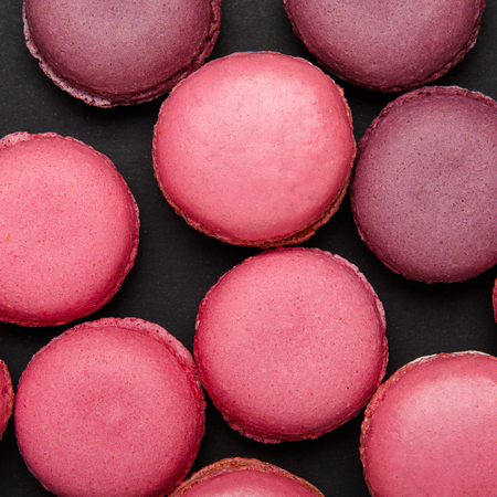 Multicolored pink macaroon on a black background, texture. Sweet treat, biscuits, high-calorie food. Copy space, top view, flat lay
