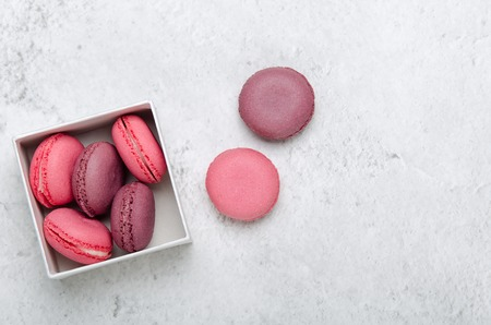 Pink macaroon cookies on a stone background in box. The concept of sweets, pastries, junk food. Minimal composition. Top view, flat lay. Stock fotó