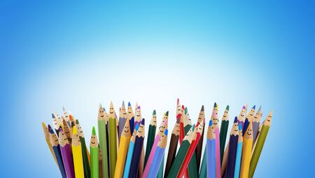 Colored pencils as faces of smiling children. Group of happy children. Friendship and communication children. kindergarten. Community of children with different ethnicity and culture. Copy space Stock Photo