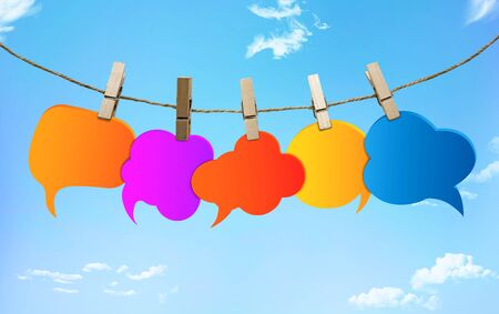Gossip. Speech bubble various colors. Chatter speaking and communication. Social network. Information. Group of empty balloons. Clouds hanging from a rope with clothespins on a blue background