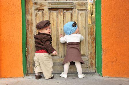 gemelos ni�o y ni�a: gemelo chico y chica de pie en la puerta Foto de archivo