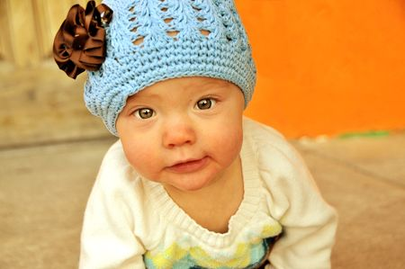 Baby girl with crochet hat and flower crawling. Reklamní fotografie
