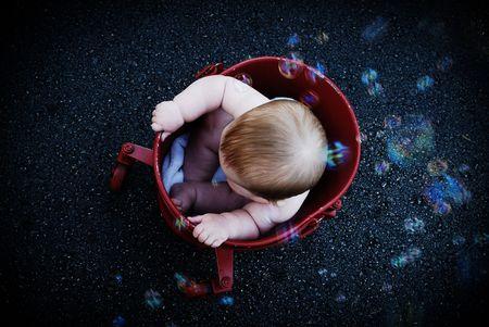 baby met bellen in bucket bovenaanzicht. Stockfoto
