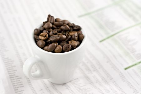 Classic espresso cup on financial pages, shallow depth of field