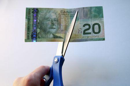 canadian cash: Cutting a Twenty with scissors Stock Photo