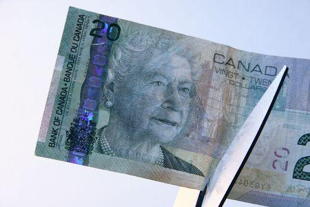 cutting costs: Cutting Costs - Cutting a Canadian twenty dollar bill with sissors