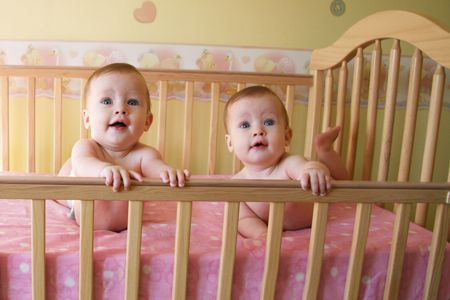 Twins in crib, twin baby girls - together Stock Photo