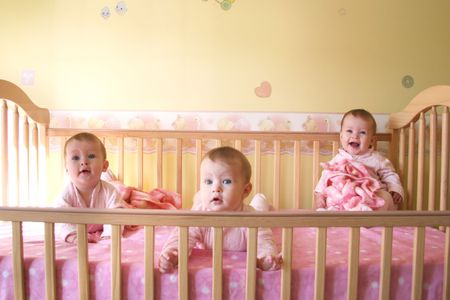Little Baby Girls in crib together - Triplets Stock Photo