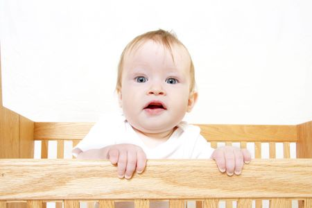 Little Baby holding onto side of crib Stock Photo - 657699