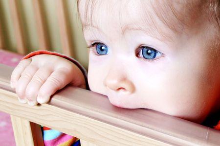 Little  standing in crib bitting on rail