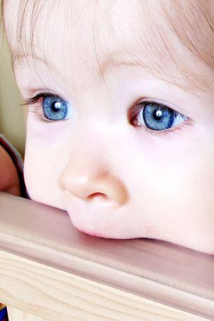 Little Baby biting on crib, taken closeup