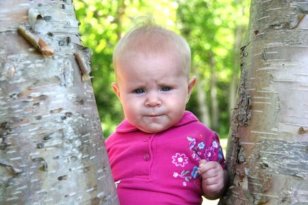 generration: Little Baby Girl posing by a tree in summer