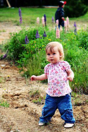 generration: Little  girl walking outside with boy in background Stock Photo