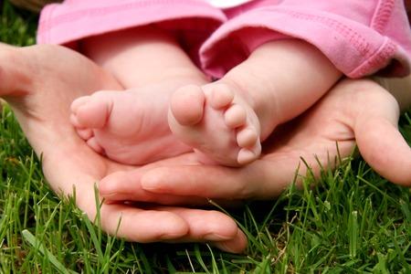 cradling: Mothers hands cradling her infant Daughters feet Stock Photo