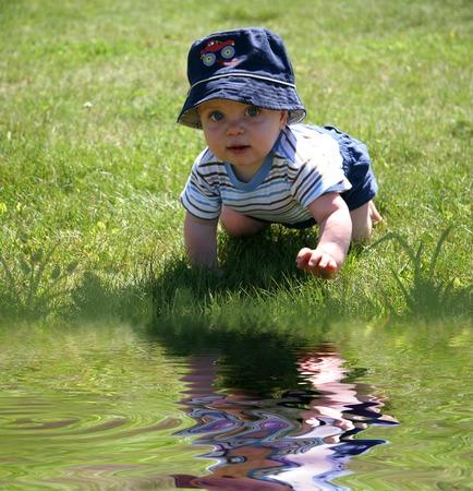 Little Boy kruipen in het gras aan het Water Stockfoto