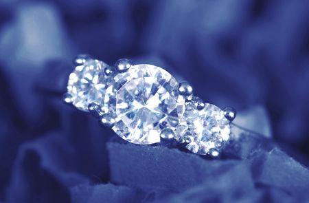 Verlovings ring genomen close-up op blauw  Stockfoto