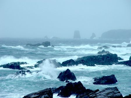 Storm in Newfoundland Ocean with waves crashing over rocks photo