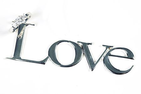 silver background: word LOVE in silver metal with ring on white Stock Photo