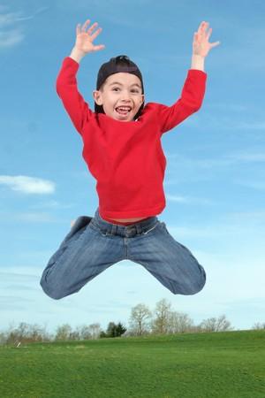 Little boy jumping in air in field photo
