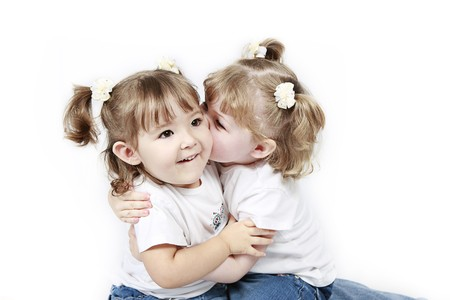 Adorable little twin girls kissing isolated on white background  photo