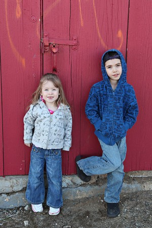 Young children hanging out near a grungy wall  photo