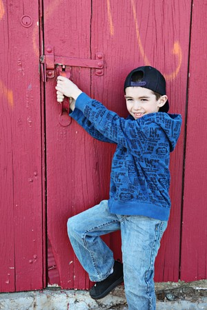 Young child hanging out near a grungy wall  photo