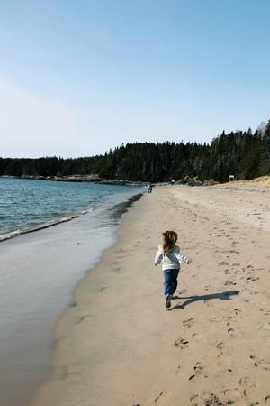 Little Girl running on beautiful beach in newfoundland photo