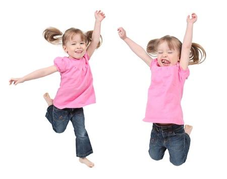 Schattig en gelukkig weinig meisjes springen in de lucht. geïsoleerd op witte achtergrond  Stockfoto