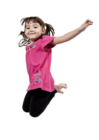 Niña poco adorable y feliz saltando en el aire. aislados en fondo blanco  Foto de archivo - 8951878