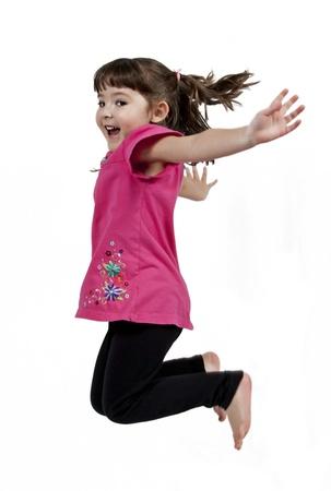 ni�os bailando: Ni�a poco adorable y feliz saltando en el aire. aislados en fondo blanco