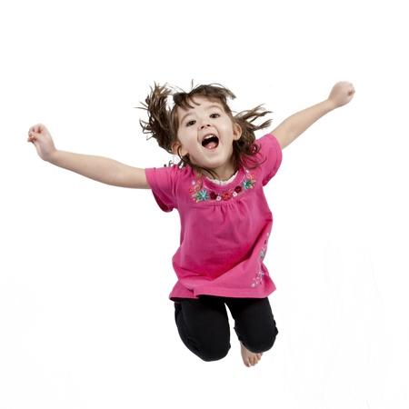 ni�o modelo: Ni�a poco adorable y feliz saltando en el aire. aislados en fondo blanco