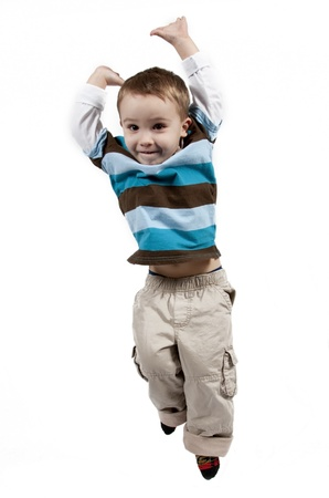Adorable and happy little boy jumping in air. isolated on white background