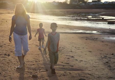 ni�os caminando: madre e hijos caminando en la playa en la puesta de sol Foto de archivo